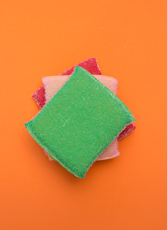 Top view of three different colours of cleaning sponges on an orange background
