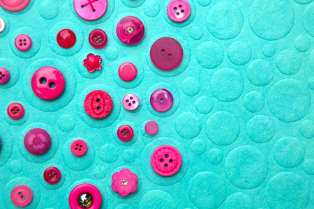 Collection of 2 and 4 holes pink buttons on a turquoise background with texture