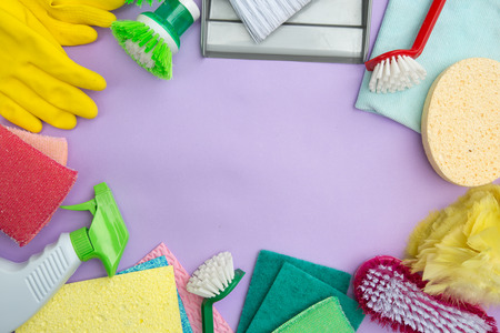 Housework.  Cleaning items like brush, gloves and cleaning spray on a purple background Stock Photo