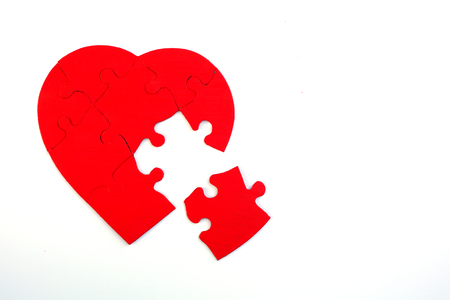 Red puzzle heart with missing piece on white background