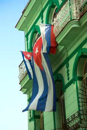 Cuban flag floating in the air against a green neoclassical building in Havana in Cuba