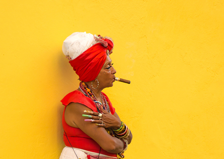 HAVANA-CUBA- DEC 4, 2018:  Woman with a cigar in her mouth with a yellow background letting tourists take photos of her for a few pesos in Havana street in Cuba