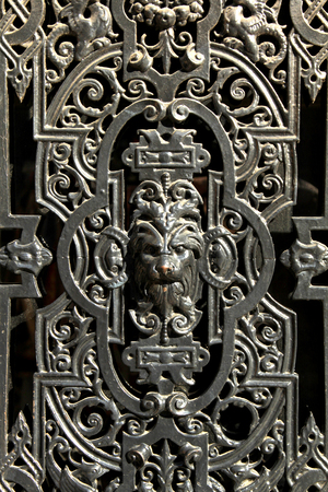 Parisian decorative metal door window in black colour with a lion face in the middle 免版税图像