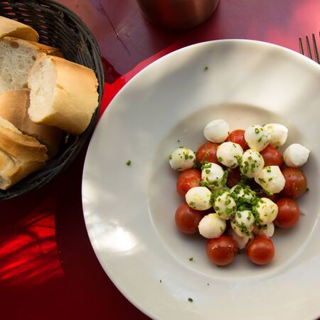 Top view of a delicious and fresh caprese salad, a tomato salad with bocconcini with fresh bread.