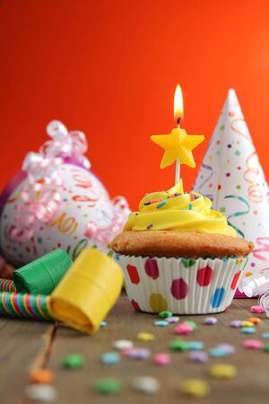 Vanilla cupcake with yellow frosting and a birthday candle with hats and blower on a wooden table Standard-Bild