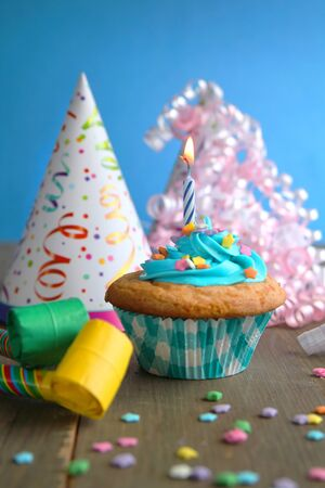 Vanilla cupcake with blue frosting and a birthday candle with hats and blower on a wooden table and a blue background Standard-Bild