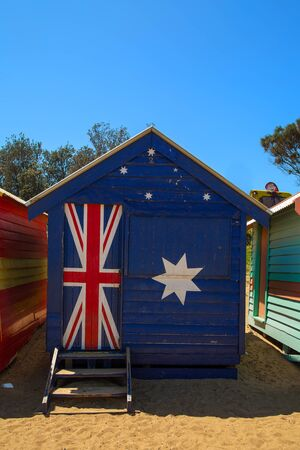 Traditional and colourful little beach house with the australian flag at Brighton beach in Victoria, Australia