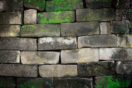 Old stone brick wall with moss photo
