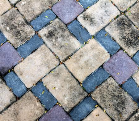 dried leaf: dirt brick stone block floor have little dried leaf