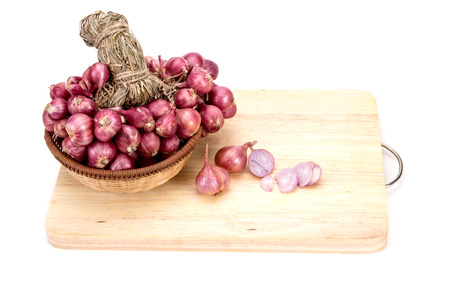 close up red onion or shallots in wooden basket on block with sliced onion on wooden chopping block