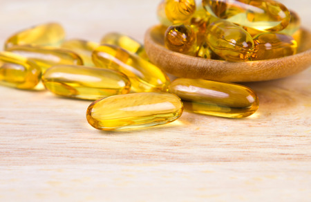 primrose oil: Closeup the yellow soft gelatin supplement fish oil capsule on wooden plate Stock Photo
