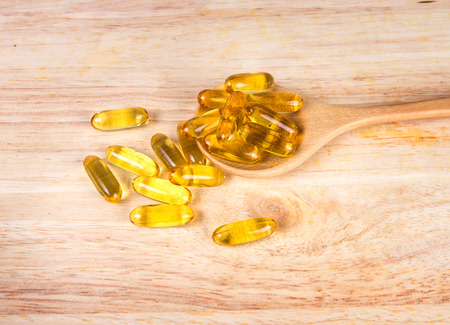 Closeup the yellow soft gelatin supplement fish oil capsule on wooden plate Zdjęcie Seryjne
