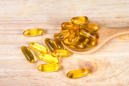 Closeup the yellow soft gelatin supplement fish oil capsule on wooden plate Archivio Fotografico