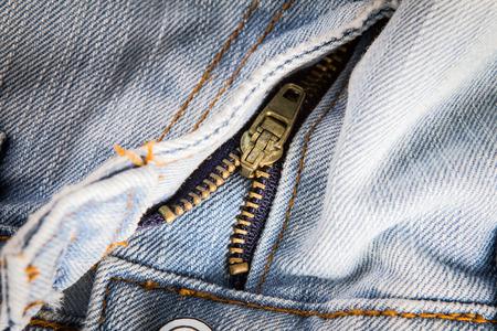 jeanswear: closeup metal zipper of the jeans pants , selective focus
