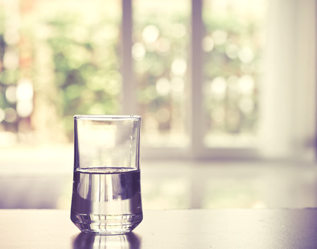 close-up Glas water op tafel in de woonkamer, vintage en retro stijl