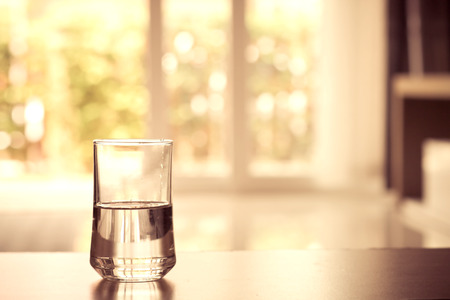 closeup Glass of water on table in the living room , vintage and retro style