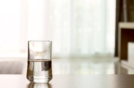 リビング ルームのテーブルの上に水のガラスをクローズ アップ