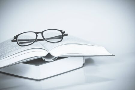 black rimmed: black rimmed glasses placed on the opened book