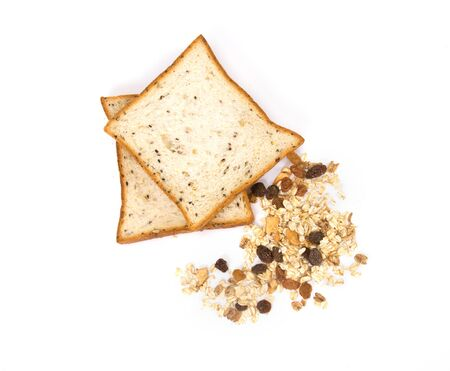 the cereal and black sesame bread with whole grain cereal flakes which mixed warming cinnamon , red skin apple , golden raisins and roasted hazelnuts on white background photo