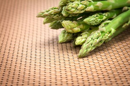 bind: Asparagus bind with brown ribbon on brown wickerwork background Stock Photo