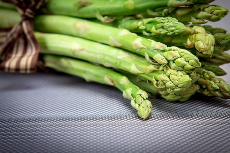 bind: selective focus of close up Asparagus bind with brown ribbon on blue grey background Stock Photo