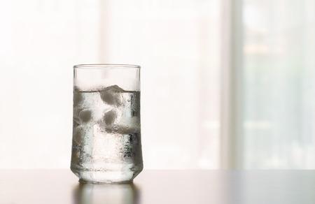 Le verre de boisson fraîche fraîche avec le cube de glace sur la table