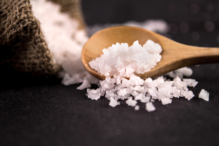 the salt crystals on black stone plate background  selective focus