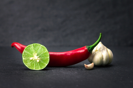 thai chili pepper: red chili , garlic and lime lemon arrange on black stone background Stock Photo