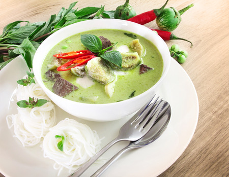 Green curry creamy coconut milk with chicken , the Popular Thai food called Gaeng Keow Wan Gai on wooden table
