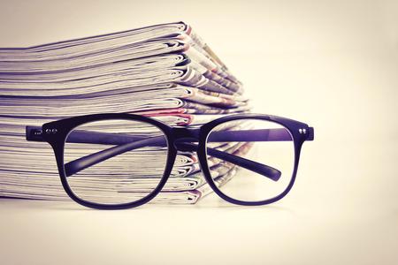 selectieve focus op het lezen brillen met het stapelen van de krant achtergrond