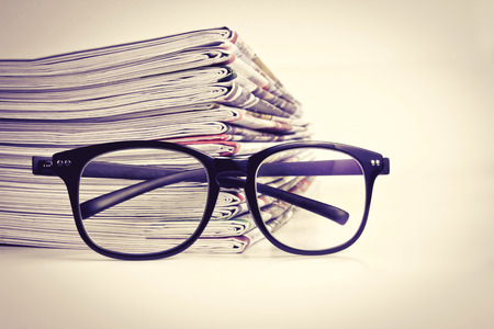newspaper: selective focus on reading eyeglasses with stacking of the newspaper background