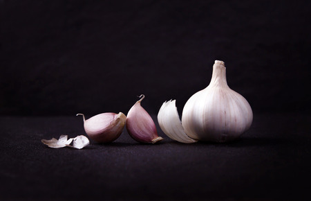 still life arrangement of Three whole garlic bulbs grouped on black stone plate Archivio Fotografico