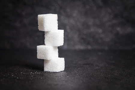 cloose up the white sugar cubes on black stone plate background Archivio Fotografico