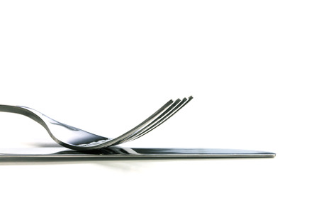 dinner plate: selective focus of close up dinning the silverware fork and knife with dish on white background and copy space for text