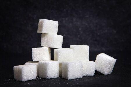 黒い石に白い砂糖の立方体を cloose プレート バック グラウンド