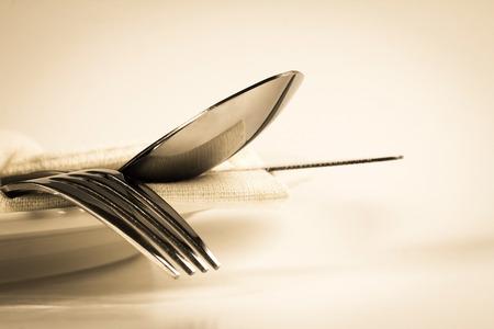 Color de la vendimia de cerca dinning el tenedor cubiertos, cuchara y cuchillo con el plato sobre fondo blanco y espacio de texto Foto de archivo - 44261313