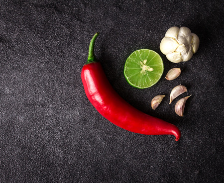 thai chili pepper: red chili, garlic and lime lemon arrange on black stone background with text space