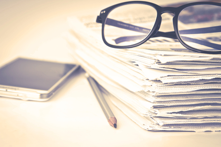 the reading eyeglasses with stacking of newspaper background