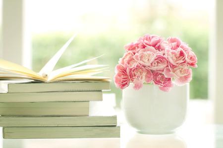 로맨스: 휴식과 로맨스 잠시 책을 읽고 배경으로 신선한 달콤한 로맨틱 핑크 카네이션 꽃,