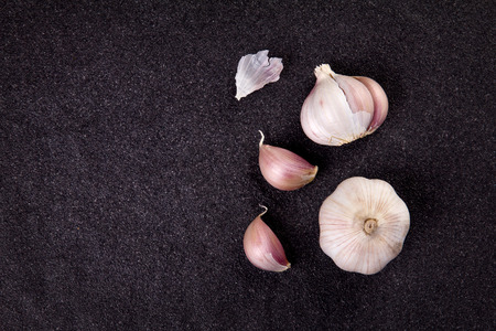 tops: still life arrangement of Three whole garlic bulbs grouped on black stone plate Stock Photo
