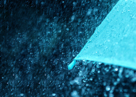 rain weather: selective focus for close up a part of the umbrella which has Rain drops falling , shallow DOF
