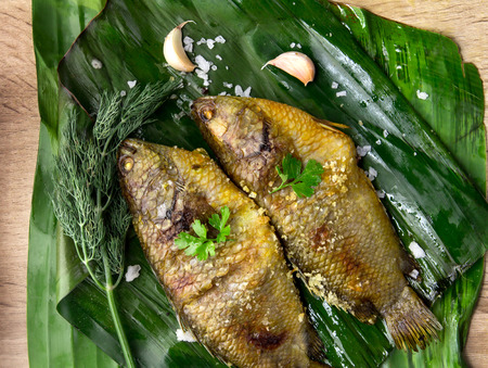 Delicious grilled fresh fish on dark stone background , healthy or diet food.