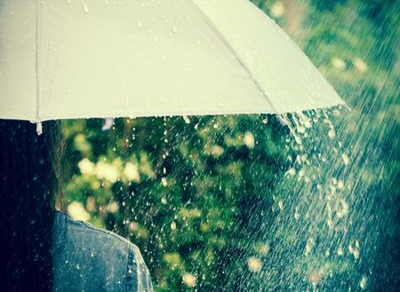 gotas de agua: cerrar una parte de la chica que se mantenga en el paraguas entre Gotas de lluvia que cae Foto de archivo