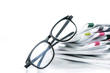 newspaper stack: selective focus on reading eyeglasses with stacking of the newspaper background ,business information concept Stock Photo