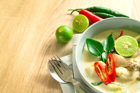 plato de comida: Sopa de coco cremosa picante con pollo, comida tailandesa llamado Tom Kha Gai en mesa de madera Foto de archivo