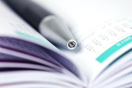 calendario escolar: selective focus of the ball pen on opened lined diary book with calendar page