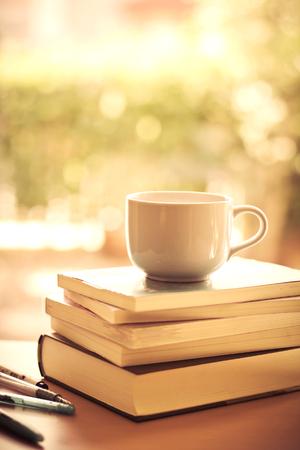 colegios: enfoque selectivo de la taza de café blanco y libros de apilamiento con el dulce fondo iluminación bokeh en la mesa