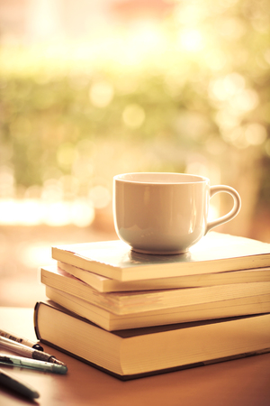 selective focus of the white coffee cup and  books stacking with sweet bokeh lighting background on  table Archivio Fotografico