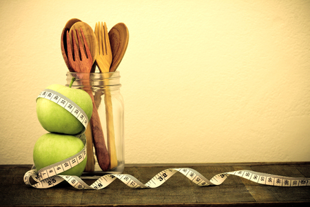 fat food: the green apple with Measuring tape and wooden spoon and fork on wooden table and concrete wall background in concept of healthy and diet , vintage color tone