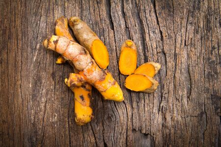 curcumin: the turmeric root on wooden plate